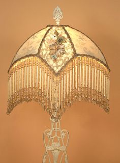 Ornate Victorian metal lamp base with flower basket motif holds a cream colored Star lampshade with victorian embroidered netting, 1920s era silver metallic lace and silk ribbon work in the center panels.  Hand beaded fringe with extra long bugle beads incorporated the colors if the shade: cream, pink, pale robin's egg blue and celadon green. Lights up beautifully and has an all over sparkle.