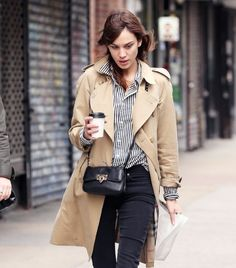 Alexa Chung en jeans, chemise rayée, trench beige et mini-sac // Alexa Chung wearing jeans, a striped shirt, a beige trench-coat and a mini-bag