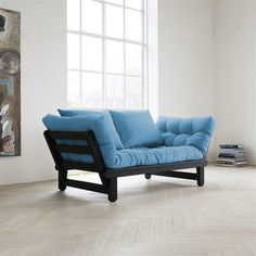 With its slanted side arms and boldly colored cushions, the Beat sofa adds a touch of drama and whimsy to any room in which it is placed. With the arms up, the