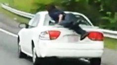 Man on trunk of car driving down highway http://www.ctvnews.ca/video?clipId=389816&playlistId=1.1891565&binId=1.810401&playlistPageNum=1
