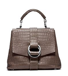 A seamless blend of tradition and trend, the Julie mixes an exotic crocodile exterior with a vintage-inspired silhouette. Sleek double-ring hardware and exposed topstitching trim the outside, while the silk-lined interior features a plethora of leather-trimmed pockets. Carry it by the top handle with a midi skirt and turtleneck sweater.