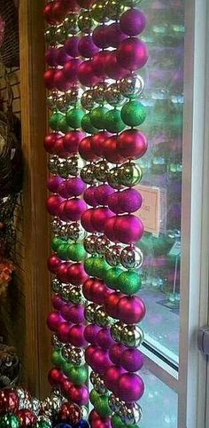 Buy cheap dollar store ornaments put fishing wire through putting a knot at each end of bulb and hang with tension rod for a holiday window treatment!
