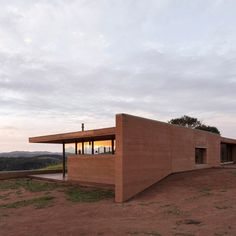 Arquipélago Arquitetos designed the flat-roofed residence to stand out on its site at the top of a gently sloping property next to a large tree that offers shade. The reddish earthen tone contrasts with verdant surroundings, but depending on the season and position of the sun, the home appears to be integrated with the landscape. Rammed Earth Homes, Rammed Earth Wall, Melbourne Suburbs, House On Stilts, Rural House, Earthship, Dezeen, Cladding, Vermont