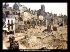 Trucks with American troops trundle into the destroyed French town of St Lo in 1944