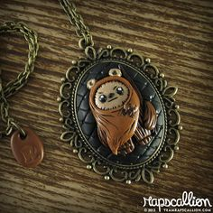 """We've imported this little Ewok straight from a galaxy far, far away...and into this fancy filigree cameo setting. This classy statement piece in out of this world!  - hand sculpted high quality polymer clay - hand painted detailing - glazed for a shiny shine - setting measures 2""""w x 2.3""""h ..."""