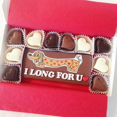 I Long For You Weiner Dog Chocolates - Say how much you want to be with that special person in a delicious and fun way! Edible and cute this little wiener dog shows how much you're thinking of them. This a great gift for either a man or a woman! Choose from milk, dark and white chocolates. Shown in mixed hearts with large milk chocolate block. Lettering is white with a red heart. By Diamond Chocolates.net