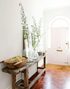 White walls and wood table with large vases