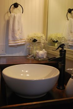 bronze water pump style faucet with white vessel sink
