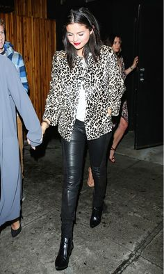 Selena Gomez wears a white t-shirt, leopard jacket, leather skinny jeans, and black boots