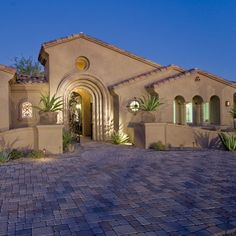 Spanish Colonial style home - through the gate in the arch opening, a lovely entry courtyard welcomes guests.