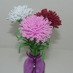 One of the worlds oldest cultivated flowers, carnations are Januarys flower. I have included in this 10 1/2 tall arrangement three of the most popular colors: white, pink, & red.  Each carnation is made from hundreds of Czech glass seed beads. The flower head is about 2 1/2 wide and is comprised of many layers. It has a green calyx & two double pairs of leaves.  French beaded flowers are created by stringing tiny seed beads on wire, forming each individual part of the flower...