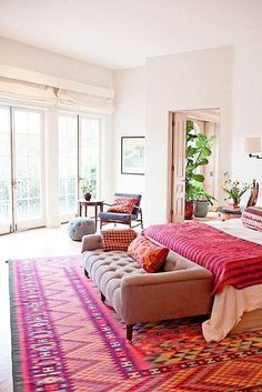 Colorful modern global design in a master bedroom featuring a large pink and orange patterned kilim rug, a velvet settee at the foot of the bed, blush pink bedding, a deeper pink striped throw blanket and ethnic patterned pillows - Global Chic & Modern Bohemian Decor - domino.com