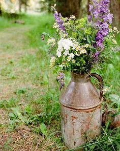 An old jug with wildflowers enhances the natural beauty of the clearing in the woods