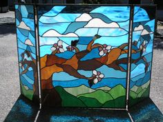 I saw this last week. A stained glass fireplace screen with a backlight. Gorgeous. Stained Glass Japanese Weeping Cherry Fireplace Screen / Window Triptich. $595.00, via Etsy.