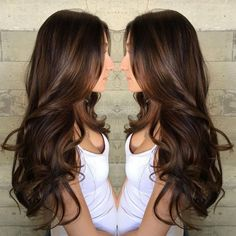 Caramel highlights on long curled chocolate brown hair