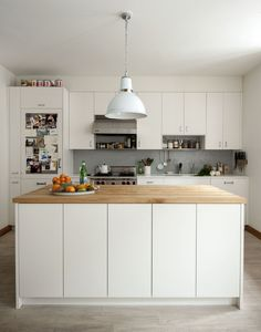 Above: In a remodeled Brooklyn kitchen by Oliver Freundlich of Oliver Freundlich Design, the island is fronted by shallow storage cabinets that have touch-latch openings so they look invisible. Brooklyn Kitchen, New Kitchen, Kitchen Dining, Kitchen Decor, Kitchen Lamps, Family Kitchen, Decorating Kitchen, Kitchen White, Kitchen Ideas