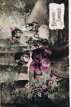 豪華な衣装に身を包み、花の咲き乱れる森の中にたたずむ二人の美しい少女のポストカード。モノクロの写真にほのかな色付けが施された幻想的な雰囲気です。アンドレへMBより新年のあいさつを兼ねたノエルのカードで…