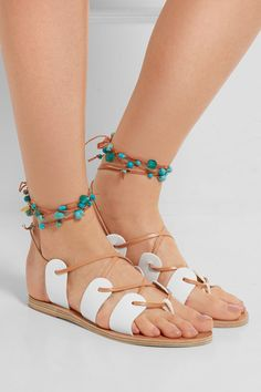 Handmade in Greece from supple white leather, Ancient Greek Sandals' 'Amaryllis' sandals are finished with a lace-up front and braided tan ankle ties. Show off the colorful array of cabochons and ornate gold coins with midi and mini hemlines.