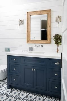 Welcoming white and blue bathroom boasts a wood beveled mirror hung between Arteriors Sabine Sconces mounted to a white shiplap wall over a navy blue washstand placed on white and blue mosaic floor tiles. Blue Bathroom Vanity, Navy Blue Bathrooms, Blue Vanity, Wood Bathroom, Bathroom Renos, Bathroom Flooring, Bathroom Ideas, Bathroom Plans, Bathroom Remodeling