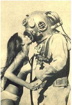 Girl kissing hardhat diver.