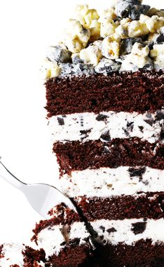 Feast your eyes (and mouth) on this Triple Stuffed Oreo Layer Cake topped with Homemade White Chocolate Popcorn. #BiteMeMore #recipes