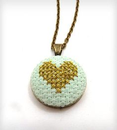 Cross Stitch Heart Necklace | On a mint cotton background, stitches of gold metallic embroid.