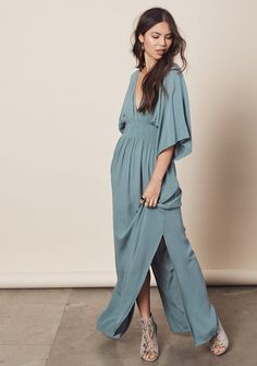 Effortlessly chic, double v-neck, kimono sleeve maxi dress featuring side slits, smocked waist and tie neck detail. 100% Rayon GauzeModel...