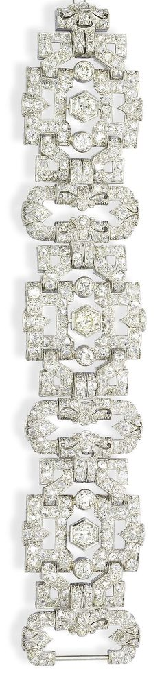 AN ART DECO DIAMOND BRACELET  The openwork wide band of geometric design, set with three old-cut diamond rectangular panels, each centering upon a larger old-cut diamond, alternating with diamond buckle link spacers, mounted in platinum, circa 1930