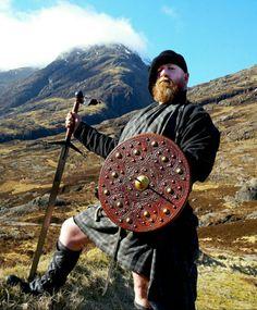 Wearin' a fèileadh mòr an' a boineid while holdin' a claidheamh-mòr an' targe at Innean a' Cheathaich (The Study) in Glencoe.