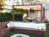 An outdoor wooden banquette offers a cozy gathering place around the fire pit in this backyard design created by Chris Lambton for HGTV's Yard Takeover.