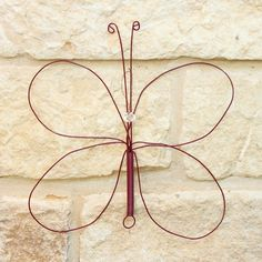Turn a thrifted whisk into piece of garden decor that's shaped like a butterfly.