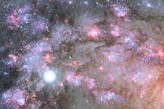 Representación artística de un núcleo galáctico ardiendo con la luz de millones de estrellas recién nacidas