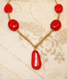 Vintage KJL Kenneth Jay Lane Red Orange Bead Pendant Drop Necklace Vintage is designed with gold plated chain and a large drop style pendant with 3 evenly placed acrylic style beads on each side of th