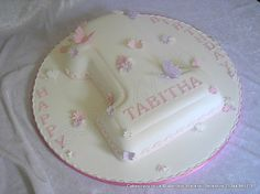 Large number one numeral shaped birthday cake covered in in an ivory coloured icing and decorated with simple pink and purple butterflies and flowers