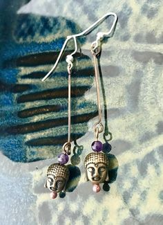 Take a deep breath in and exhale. Thats the feeling youll have with these peaceful Buddha earrings accented with a tiny amethyst bead which represents enlightenment and the crown chakra. Hung on hypoallergenic ear wires, these earrings measure approximately 1 3/4 Inches in length. Handmade with copper wire, amethyst and copper beads. These dainty swaying earrings are truly beautiful.