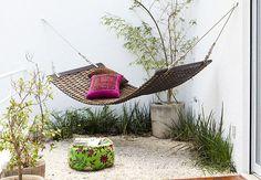 A varanda da suíte de casal tem rede de madeira articulável pendurada e pufe florido. Projeto da arquiteta Simone Mantovani  Edu Castello / Casa e Jardim