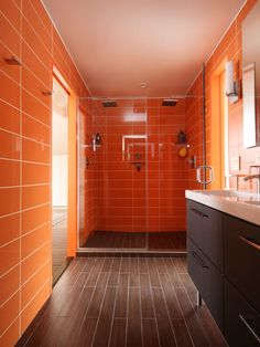 Roca wall tile in Rainbow Azul creates a citrus color scheme and the floor is clad in ceramic plank. Sinks and faucets are Ikea.