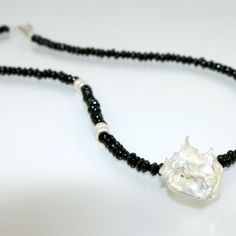 This one of a kind necklace is made from sterling silver and black tourmaline beads with a unique free form sterling silver centre piece . The necklace is finished with a handmade sterling silver hook. It can be worn day or evening, adding glamour to every outfit.