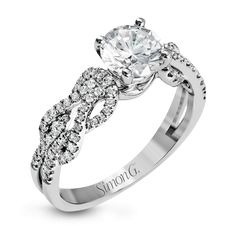 This distinctive 18k white gold ring has an intricate design reminiscent of lover's knots and eternity symbols, set with .33 ctw of white diamonds.