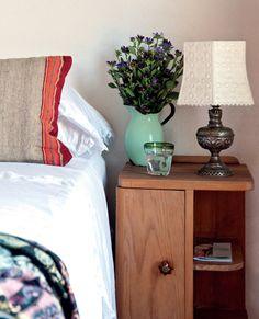 Un close up para este rincón de la habitación principal. Sobre la cama vestida con sábanas de algodón y puntillas, un almohadón con género del Norte da la nota de color (Hecho a mano). La mesa de luz años '60 le da sostén a un simpático velador armado con un pie de bronce (de un anticuario de Cariló) y una pantalla de tela calada (Casa Chic).