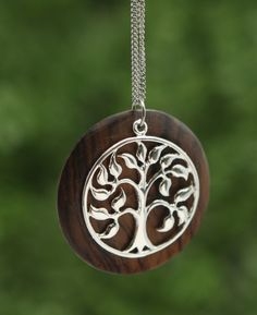 Stainless steel necklace features a wood and metal pendant depicting the Tree of Life symbol. 21 inches long total.