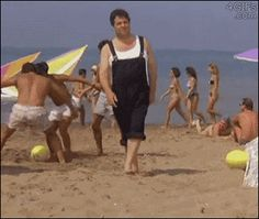 A man mistakes a guy's head on the ground for a beach ball and hurts his foot when he kicks it