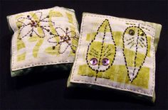 Hand sewn small sachet pillows filled with fragrant herbs. Pillows are constructed with flaps that snap in back to make them easily refillable. Fabric squares on front are rubber stamped, then appliqued and embroidered. Made from recycled fabric by Carolyn Hasenfratz.