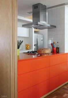 A bancada de Silestone e os módulos laqueados compõem um único bloco laranja, projetado pelo Estúdio Cláudio Resmini e executado pela Leffa Móveis.