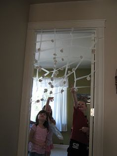 """masking tape """"spider web"""" with cotton balls. could built a really big one in the playroom."""
