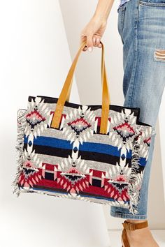 Southwestern-printed tote with genuine leather shoulder straps and fringe side detailing