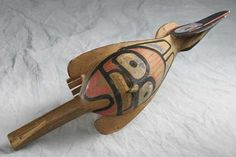 Wood rattle made by Native Americans of the Northwest Coast. Carved shape is of a raven. Adorned with painted decorations of an eagle, a frog and a human.