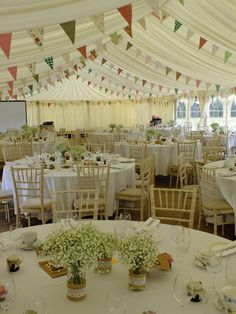 Vintage style wedding marquee with bunting and clouds of gypsophila in jam jars.
