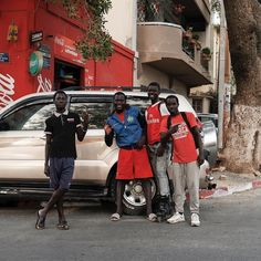 Teenage boys pose in front of a store. Dakar, Sénégal.
