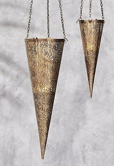 boho gleam. Gold lantern brings festive boho vibes to any outdoor space. Perfectly punctured with tiny holes, elongated metallic cone twinkles from a single tea light. Thin gold chain hangs lantern low above the table/from the trees. Super dramatic (in the best way) in multiples. CB2 exclusive.